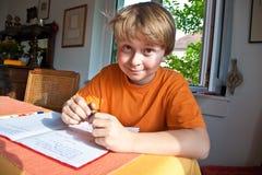 Muchacho que hace la preparación para la escuela Imagen de archivo libre de regalías