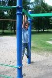 Muchacho que hace pivotar de una barra en un parque Fotografía de archivo