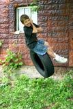 Muchacho que hace pivotar en un neumático Foto de archivo libre de regalías