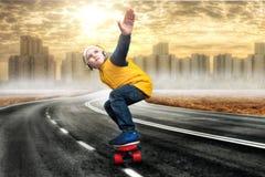 Muchacho que hace trucos en un monopatín, patín en el camino El niño pequeño en el estilo del hip-hop El golpeador joven Refresqu Foto de archivo
