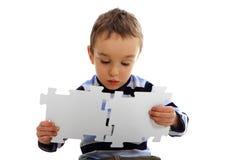 Muchacho que hace un rompecabezas en el fondo blanco Foto de archivo libre de regalías