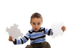 Muchacho que hace un rompecabezas en el fondo blanco Fotos de archivo libres de regalías