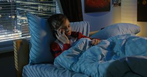 Muchacho que hace una llamada mientras que miente en cama almacen de metraje de vídeo