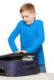 Muchacho que intenta cerrar el bolso del equipaje por completo de la ropa Foto de archivo libre de regalías