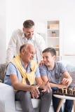 Muchacho que juega a ajedrez con el abuelo Foto de archivo