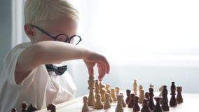 Muchacho que juega a ajedrez en la tabla metrajes
