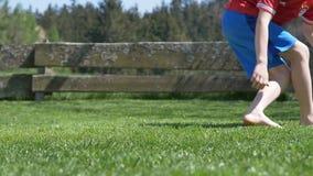 Muchacho que juega al fútbol que golpea el fútbol con el pie en jardín descalzo almacen de metraje de vídeo