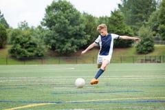 Muchacho que juega al fútbol - retroceso de la bola con el pie Fotografía de archivo