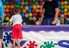 Muchacho que juega al juego del carnaval de los dardos Foto de archivo libre de regalías