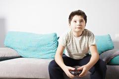 Muchacho que juega al juego video fotografía de archivo