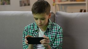 Muchacho que juega al videojuego en smartphone en casa, apego del artilugio en edad joven almacen de metraje de vídeo