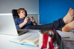 Muchacho que juega al videojuego en vez de estudiar Foto de archivo libre de regalías