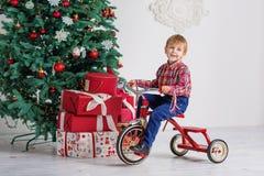 Muchacho que juega cerca del árbol de navidad Imagen de archivo