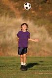Muchacho que juega con el balón de fútbol en caída Imagen de archivo