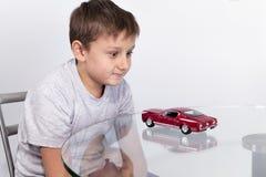 Muchacho que juega con el coche de deportes rojo en una tabla de cristal Imágenes de archivo libres de regalías