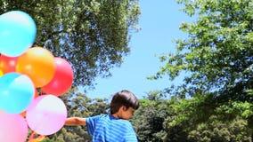 Muchacho que juega con el globo de goma en un parque almacen de video