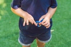 Muchacho que juega con el hilandero de la persona agitada Hilandero de giro del niño en el patio Fondo enmascarado Foto de archivo libre de regalías