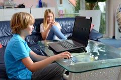 Muchacho que juega con el ordenador y su hermana que usa smartphone Fotografía de archivo libre de regalías