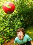 Muchacho que juega con el soplo de la cabeza del fútbol del entrenamiento de la bola Foto de archivo
