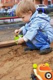 Muchacho que juega con la arena Imagen de archivo