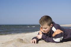 Muchacho que juega con la arena de la playa Fotos de archivo