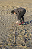 Muchacho que juega con la arena en la playa Fotos de archivo