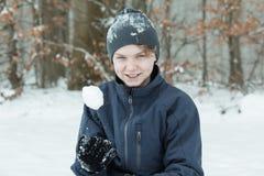 Muchacho que juega con la bola de nieve afuera Foto de archivo libre de regalías