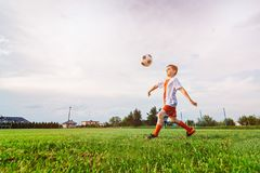 Muchacho que juega con la bola del fútbol en terreno de juego Fotos de archivo libres de regalías