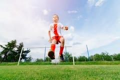 Muchacho que juega con la bola del fútbol en terreno de juego Fotografía de archivo