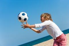 Muchacho que juega con la bola en la playa. Fotos de archivo libres de regalías