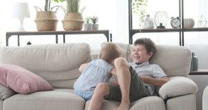 Muchacho que juega con la hermana del bebé en el sofá almacen de metraje de vídeo