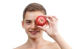 Muchacho que juega con la manzana roja, aislada en blanco Imagen de archivo libre de regalías