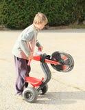 Muchacho que juega con la moto de los niños Fotografía de archivo