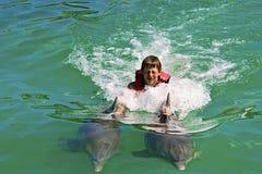Muchacho que juega con los delfínes en el mar Imagenes de archivo