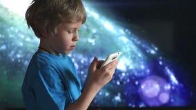 Muchacho que juega con smartphone muchacho y dispositivo móvil en las manos que se sientan en el fondo del cielo cósmico almacen de metraje de vídeo