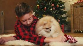 Muchacho que juega con su perro el Nochebuena almacen de metraje de vídeo