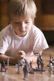 Muchacho que juega con Toy Soldiers On Floor Fotografía de archivo libre de regalías