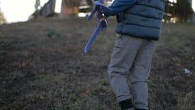 Muchacho que juega con un avión del juguete en el parque en un día soleado almacen de video