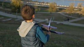 Muchacho que juega con un avión del juguete en el parque en un día soleado metrajes