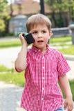 Muchacho que juega con un Walkietalkie en una calle en un ingenio del patio imagen de archivo