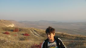 Muchacho que juega con una espada de madera en un fondo del paisaje de la montaña metrajes