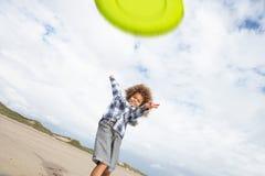 Muchacho que juega el disco volador en la playa Fotografía de archivo