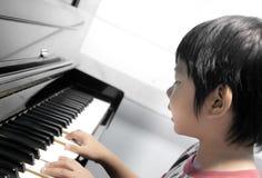 Muchacho que juega el piano Foto de archivo libre de regalías