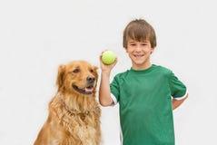 Muchacho que juega el retén con el perro fotografía de archivo