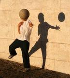 Muchacho que juega el retén con su sombra Fotografía de archivo