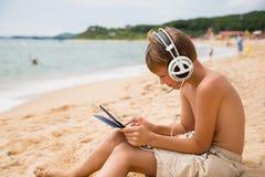 Muchacho que juega el Tablet PC que se sienta por el mar Imagen de archivo