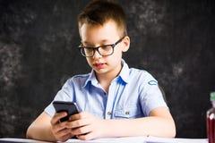 Muchacho que juega el teléfono mientras que hace la preparación Fotos de archivo
