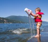 Muchacho que juega en el lago Imagen de archivo libre de regalías