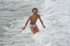 Muchacho que juega en el mar Imagenes de archivo