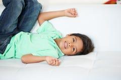 Muchacho que juega en el sofá foto de archivo libre de regalías